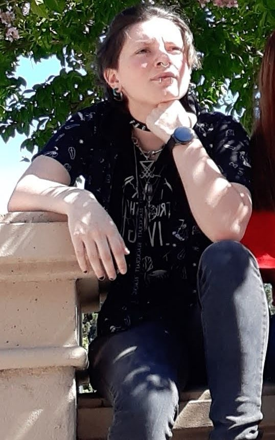 This is me, Vamp. I am wearing black jeans, a black shirt with a black Hawaiian shirt layered on top. In the photo I am also wearing a few chokers and necklaces.