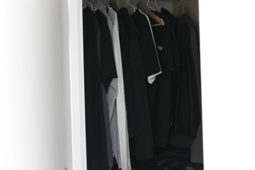Photo of clothes hanging neatly in a closet.