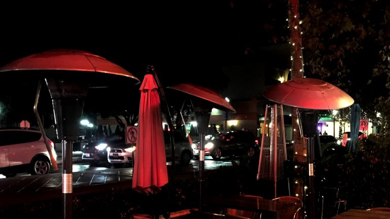 Streetside dining lit in red lights.
