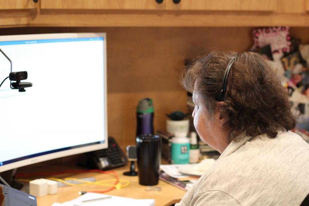 A picture of a womanwearing a headset with brown hair sits in front of a large computer monitor. There are two coffee cups in the background along with scattered cords and other papers.