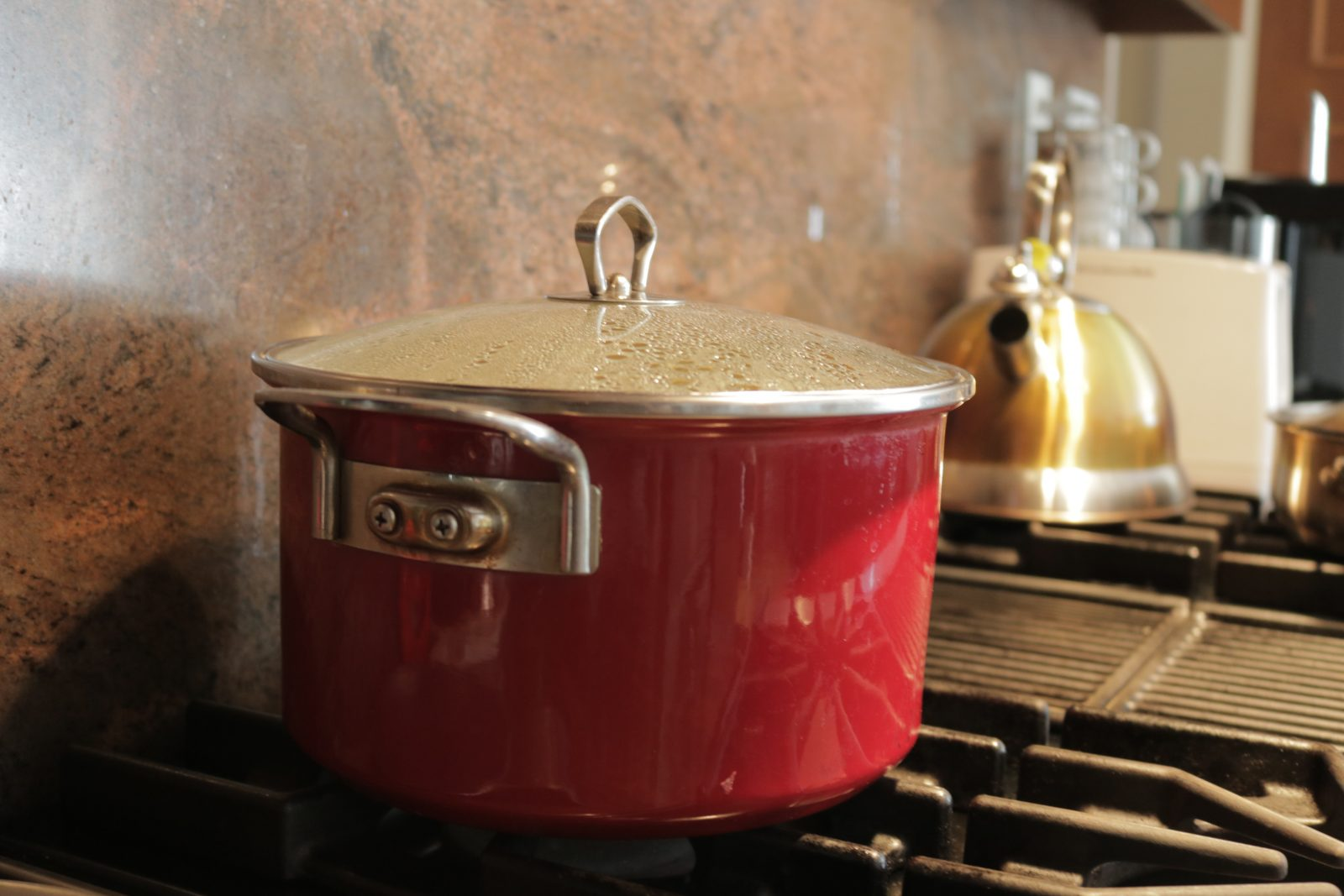 A red pot on a stove.